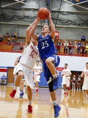 Franklin's Andrew Hartkorn (25) goes up for a layup in front of Center Grove's Trevor Harrell (12) after a steal during their sectional semifinal at Martinsville.