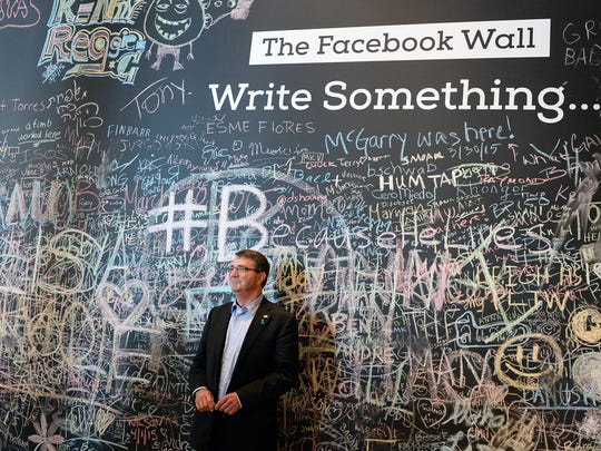 SD Ash Carter stands in front of the Facebook wall during his recent trip to their headquarters