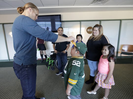 Green Bay Packers linebacker Clay Matthews gives a hat to 8-year-old Angel Cruz as his family looks on during a recent gathering to kick off the Catch A Star campaign.