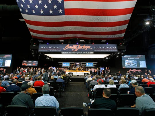 Visitors watch as a 1981 Chevrolet C-10 Pickup rolls across the auction block at the Barrett-Jackson collector car auction Monday, Jan. 16, 2017 in Scottsdale, Arizona.