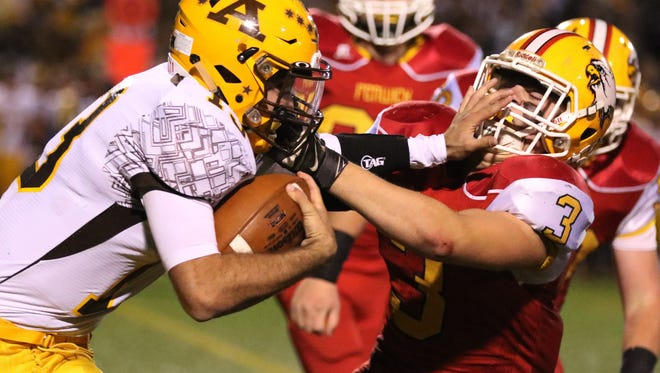 Archbishop Alter High School's Ryan Markoff, 13, left, pushes off Fenwick High School's Sammy DeBiasi, 3, during the first half of their football game played in West Carrollton, Ohio Saturday, November 14, 2015.