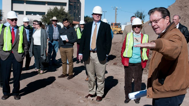 Bob Pofahl, of Las Cruces Community Partners, shows members of the Las Cruces City Council the approximate height of the proposed stage at the construction site for the downtown plaza Monday afternoon. Gary Mook/ for the Sun-News
