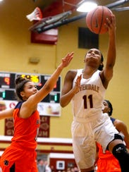 Riverdale's Aislynn Hayes (11) goes up for a shot as Blackman's Jaida Bond (10) defends her Friday.