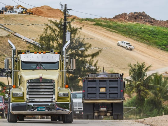 Dump trucks and other vehicles are photographed as they enter and leave the site of the former Ordot landfill in this Feb. 3, 2015, file photo.