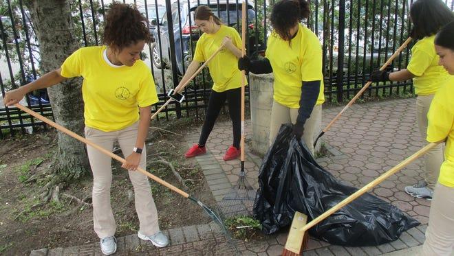 Eastside students cleaning the sidewalk around their school