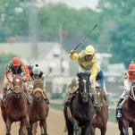Jockey Patrick Valenzuela aboard Sunday Silence raises his crop after crossing the finish line to win the 115th running of the Kentucky Derby on May 6, 1989 in Louisville, Ky.  (AP Photo/Jim Gerberich)