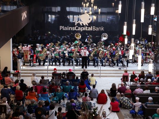 "More than 80 tuba, euphonium, baritone and sousaphone musicians ages 12 to 71 perform during the 28th annual Tuba Christmas in the lobby of the Plains Capital Bank on Friday, Dec. 22, 2017. ""The whole impetus for Tuba Christmas is often tuba and euphonium players only play one or two together,"" Dan Sipes said, one of three conductors."