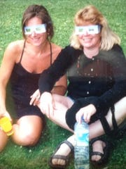 Oxnard resident Anita Smith, right, wearing solar eclipse