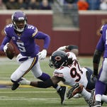 Minnesota Vikings quarterback Teddy Bridgewater (5) tries breaking away from Chicago Bears outside linebacker Willie Young (97) during the first half of an NFL football game Sunday in Minneapolis.