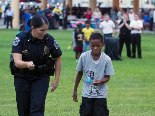 Fort Myers police Lt. Rebecca Prince helps Danny Barksdale with the egg race on Tuesday at National Night Out at Centennial Park in Fort Myers, co-sponsored by the Police Department and the National Association of Town Watch.