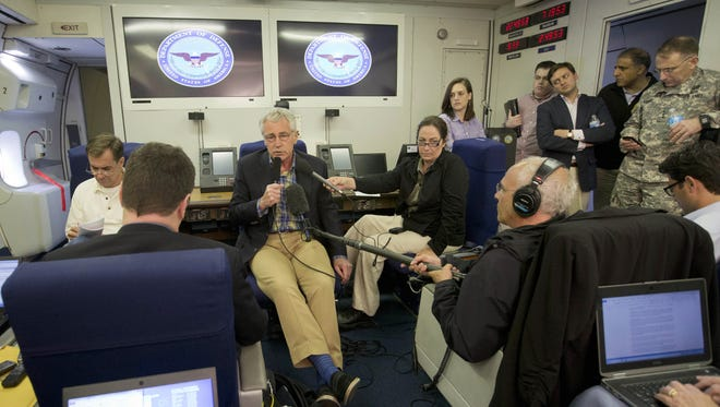 US Defense Secretary Chuck Hagel, center, speaks to media aboard a US military aircraft during a flight on June 1, 2014.