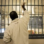 An inmate cleans bars at a guard station in Tucker, Ark., in 2009.
