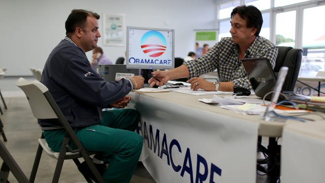 Ariel Fernandez signs up for the Affordable Care Act (Obamacare) with help from Noel Nogues, an insurance adviser with UniVista Insurance company.