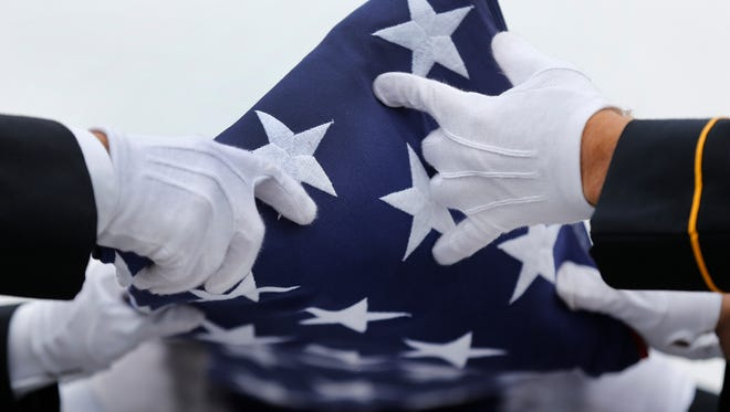 An Army honor guard folds a flag from a casket during a memorial service and burial.