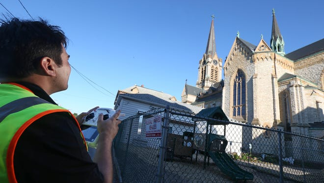 Chris Dominicos of East Bloomfield operates a small drone over St. Michael's Church in Rochester. Dominicos and Mike McBride, owner of Unmanned Aerial Systems, were using the drone to see if the church's roof had any damage.