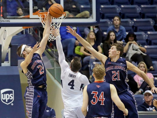 St. Mary's Calvin Hermanson, left, and Evan Fitzner (21) defend BYU guard Nick Emery (4) during the second half of an NCAA college basketball game Saturday, Feb. 18, 2017, in Provo, Utah. Saint Mary's won 70-57. (AP Photo/Rick Bowmer)