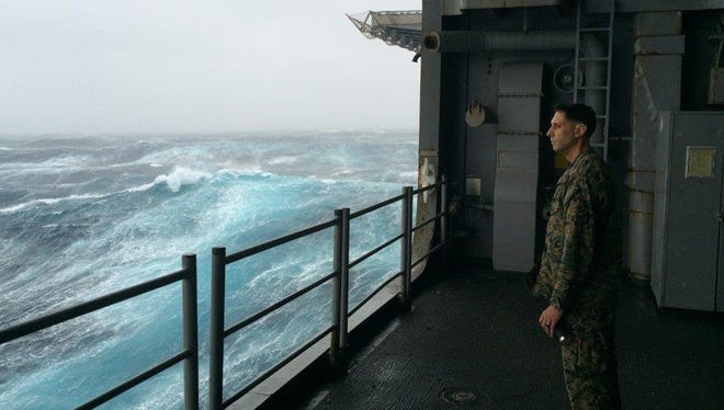 In this Sunday, Oct. 9, 2016 photo, Marine Gunnery Sgt. Jeremiah Benjamin, 34, of San Diego, watches the Atlantic churn aboard the USS Iwo Jima. Benjamin is among a group of Marines and sailors bound for Haiti to help out with relief efforts following Hurricane Matthew's destruction.