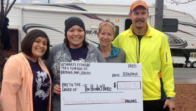 Healing House staffers, from left, Julie Flores and Irene Trejo hold a check for $6,500 donated by Shannon and Joel Stevens, founders and organizers of the 13th annual Turkey Trot held Thanksgiving Day at Voiers Park. The three-mile run, two-mile walk and one-mile kids' fun run generated the money donated to the Healing House, Luna County's shelter for survivors of domestic violence.