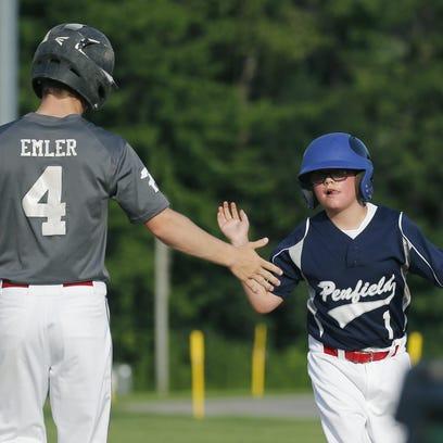 Dylan Emler high-fives bat boy D.J. Teeter after picking