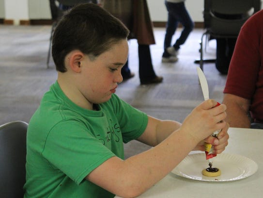 Hunter Buchanan, 9, carefully concentrates as he decorates