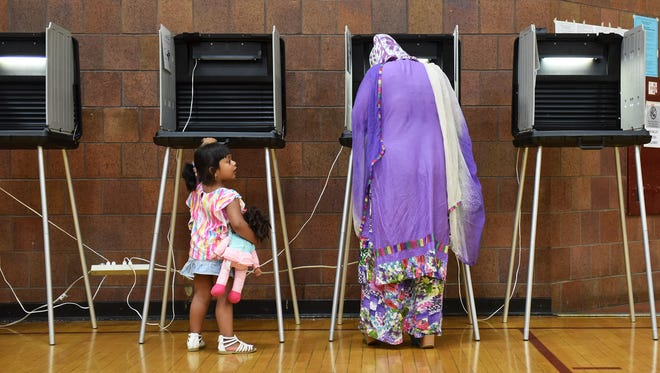 Farnaz Anaum, 3, looks at her mother, Farzana Akhter while she fills out her ballot for precinct 3 at the polling center at Hamtramck High School in Hamtramck, Mich. on Aug. 8, 2017.