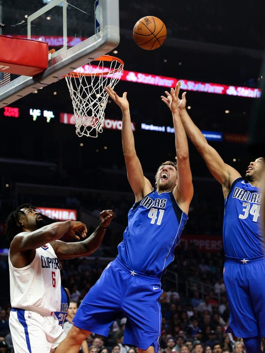 Dallas Mavericks forward Dirk Nowitzki, center, and teammate Dallas Mavericks guard Devin Harris, right, fight for a rebound with Los Angeles Clippers center DeAndre Jordan during the first half of an NBA basketball game Wednesday, Nov. 1, 2017, in Los Angeles. (AP Photo/Ringo H.W. Chiu)