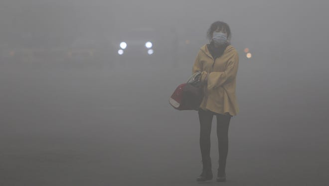 A woman wearing a face mask walks in heavy smog in Harbin.