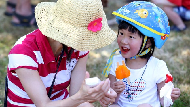 Allison Le, 4, enjoys an ice pop with her mother, Julie, after they participated in the Court-Chemeketa Fourth of July Kids Parade on Saturday, July 4, 2015.