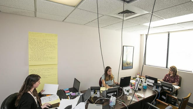 Ethernet wires come down from the ceiling as Kaitlin Brittain, from left, Rachael Shaw and Megan Jones, all graduate students from the University of Florida, work on tracking down positive COVID-19 patients on Tuesday at the Florida Department of Health in Marion County.