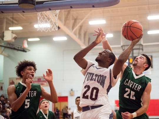 Fulton's Markeese Sheely, center, shoots against, Carter's