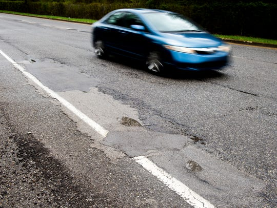 A car drives past patched potholes on North Mall Drive
