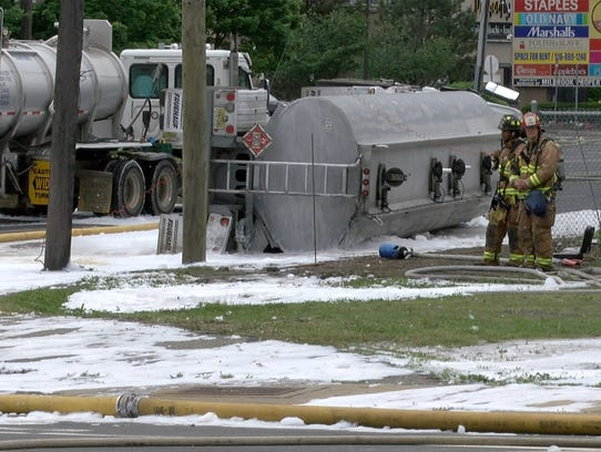 Firefighters stand by an overturned fuel truck at Route