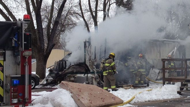 Fire crews work to control a blaze Monday afternoon at mobile home on Holiday Lodge Road in North Liberty. The home's sole occupant, 70-year-old Fred Steven, escaped unharmed.