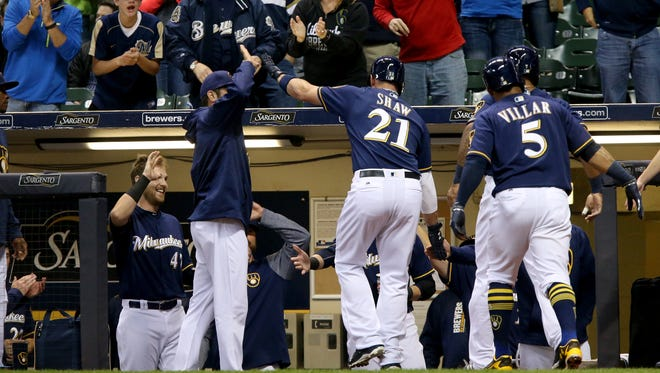 Travis Shaw #21 of the Milwaukee Brewers is congratulated by teammates after hitting a home run in the first inning against the St. Louis Cardinals at Miller Park on April 20, 2017 in Milwaukee, Wisconsin.