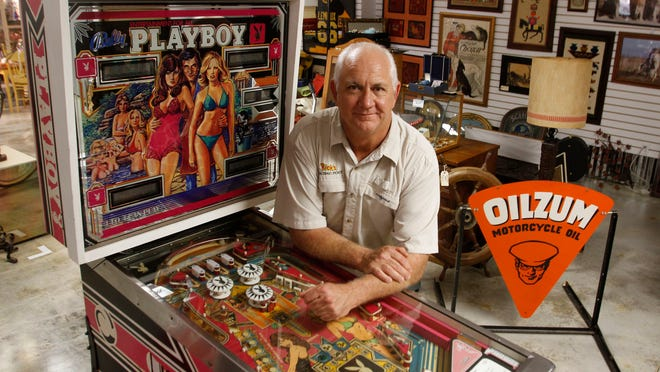 Rick Keating owner of Rick's Trading Post, near a vintage Playboy pinball machine Tuesday. His store is an eclectic mix of diverse items and home furnishings.