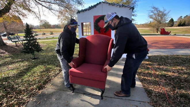 From left, Louie Grigg and Coty Flynn place a chair for Santa at Shelby City Park on Thursday.