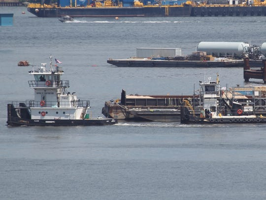 The tugboat at right is partially submerged after it