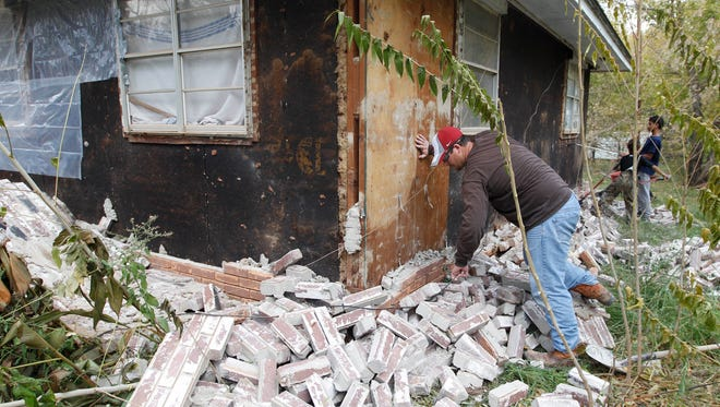 Chad Devereaux examines bricks that fell from his in-laws' home in Sparks, Okla., after two quakes hit the area in less than 24 hours in 2011. Research has linked the quakes to fracking wastewater disposal.