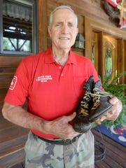 Jim Harding stands outside his Huntingdon home with his old football running shoes that he used during his time playing for the PSU Panthers in the 1950s.