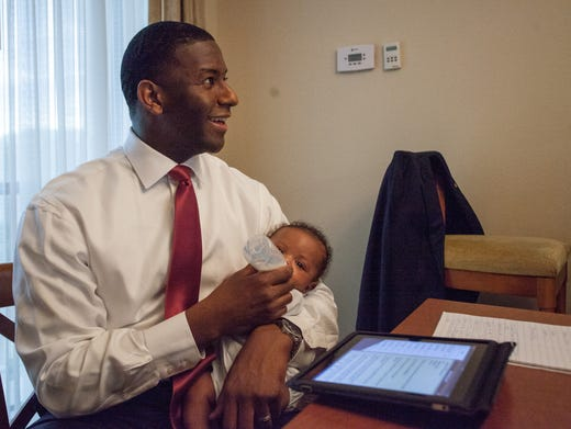 Newly elected mayor Andrew Gillum prepares his speech while feeding his 14 weeks -old son Jackson Gillum on Tuesday, 26 August, DoubleTree Hotel in Downtown Tallahassee
