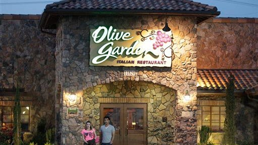 In this 2014 file photo, patrons exit an Olive Garden Restaurant in Short Pump, Va.