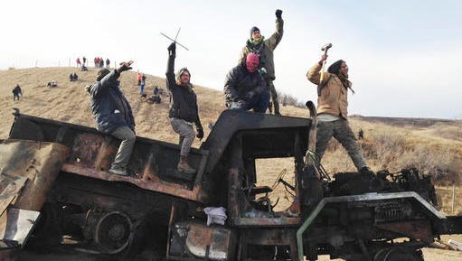 FILE - In this Monday, Nov. 21, 2016, file photo, protesters against the Dakota Access oil pipeline stand on a burned-out truck near Cannon Ball, N.D., that they removed from a long-closed bridge a day earlier on a state highway near their camp in southern North Dakota. President-elect Donald Trump holds stock in the company building the disputed Dakota Access oil pipeline, and pipeline opponents warn that Trump's investments could undercut any decision he makes on the $3.8 billion project as president.