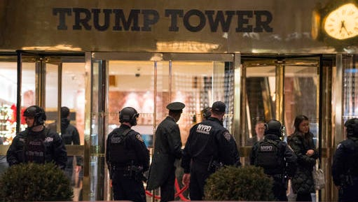 New York police officers and others stand outside the Trump Tower lobby in New York, Tuesday, Dec 27, 2016. Police hastily cleared the lobby of Trump Tower on Tuesday to investigate an unattended backpack, only to find that the bag contained children's toys