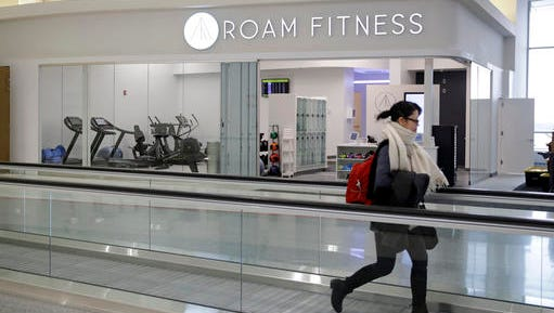 In this Jan. 30, 2017 photo, a traveler walks past the soon-to-be-open ROAM Fitness gym at Baltimore-Washington International Thurgood Marshall Airport in Linthicum, Md. Working out while waiting for your flight will soon be an option at BWI, where the only gym at a U.S. airport past security will open this week, with plans for 20 more at airports by 2020.