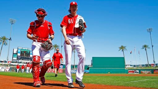 Cincinnati Reds starting pitcher Bronson Arroyo (61) walks to the dugout from the bullpen with catcher Devin Mesoraco, left, after warming up prior to a spring training baseball game against the Milwaukee Brewers Sunday, March 12, 2017, in Goodyear, Ariz. (AP Photo/Ross D. Franklin)