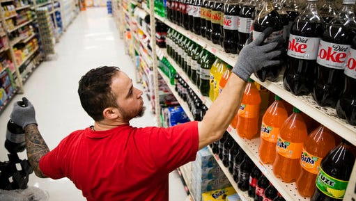 In this March 16, 2017 photo, Albert Delarosa stocks shelves with Coca-Cola products at the IGA supermarket in the Port Richmond neighborhood of Philadelphia. Less than three months into Philadelphia's new tax on sweetened drinks, the stakes have escalated: Beverage makers say the measure is hurting sales so much they need to cut jobs, while city officials say the moves are a ploy to get the tax struck down.