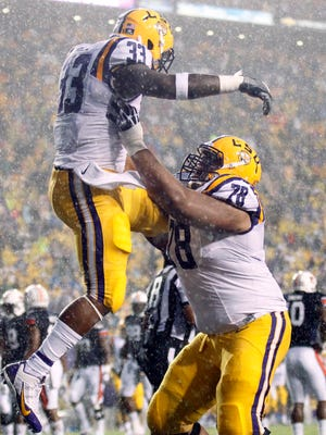 LSU's Jeremy Hill celebrates with offensive tackle Vadal Alexander after a touchdown against Auburn.