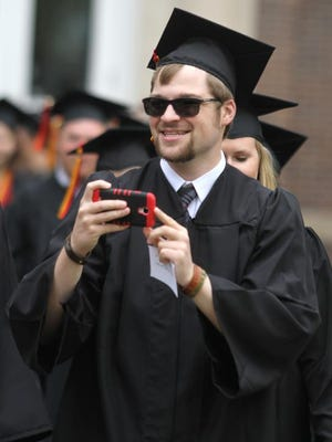 A Simpson College graduate turns his cell phone camera on the crowd of well-wishers applauding the traditional march of graduates across the campus before the graduation ceremony May 2.