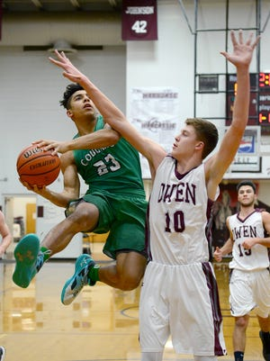 Mountain Heritage's Brandon Aumiller goes up for a shot against Owen's Mathew Brown during the semifinal game of the Western Highlands Conference tournament at Owen High School on Tuesday, Feb. 14, 2017. The Warhorses defeated the Cougars 56-55.