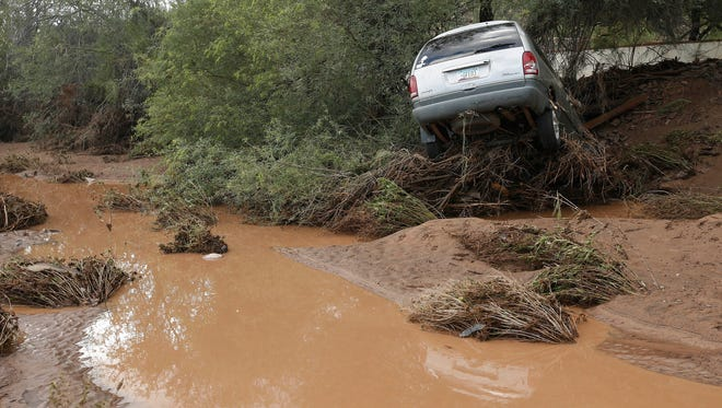A vehicle rests on top of debris after flash flood waters overran Skunk Creek after strong storms moved through, Tuesday, Aug. 19, 2014, in New River, Ariz., just northwest of Phoenix. Heavy monsoon season rains that swept across Arizona on Tuesday led to dramatic rescues, road closures and flight delays as a series of fast-moving storms pummeled the state. (AP Photo/Ross D. Franklin)